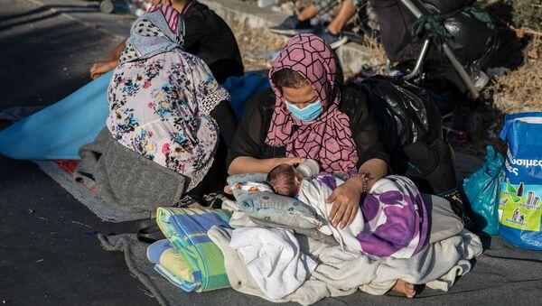 Μια γυναίκα ταΐζει με το μπιμπερό το μωρό της σε μια γωνιά του δρόμου στον δρόμο κοντά στη Μόρια, 10 Σεπτεμβρίου 2020 - Sputnik Ελλάδα