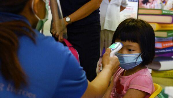Θερμομέτρηση παιδιού στη Σιγκαπούρη λόγω κορονοϊού, Ιούνιος 2020 - Sputnik Ελλάδα
