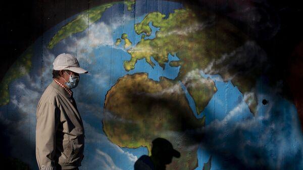Άνδρας με μάσκα μπροστά από γκράφιτι με τη Γη - Sputnik Ελλάδα