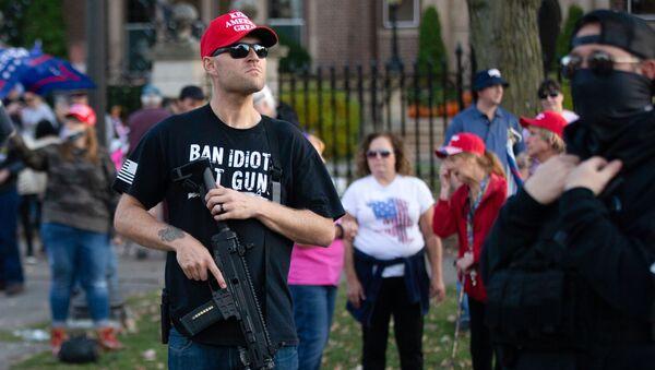 Ένοπλος υποστηρικτής του Ντόναλντ Τραμπ μποστά από την κατοικία του κυβερνήτη της Μινεσότα, Τιμ Γουόλς - Sputnik Ελλάδα