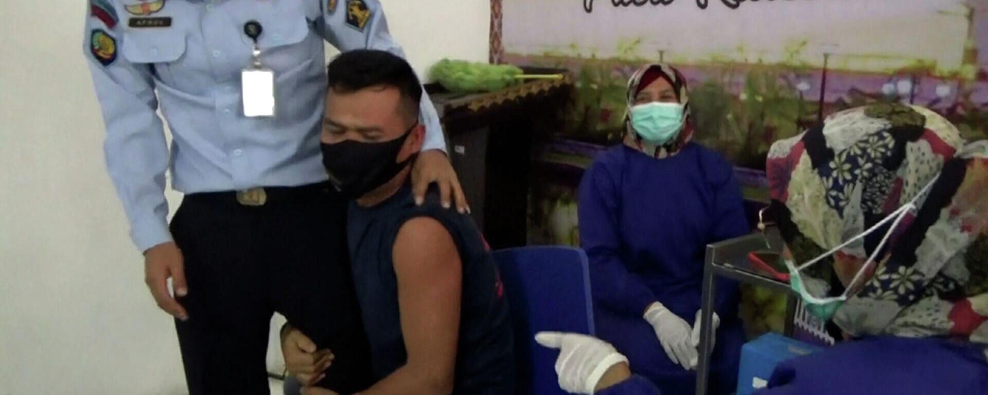 Ο τρόμος της βελόνας: Ινδονήσιος κρατούμενος γαντζώνεται από φρουρό για να κάνει το εμβόλιο - Sputnik Ελλάδα, 1920, 06.07.2021