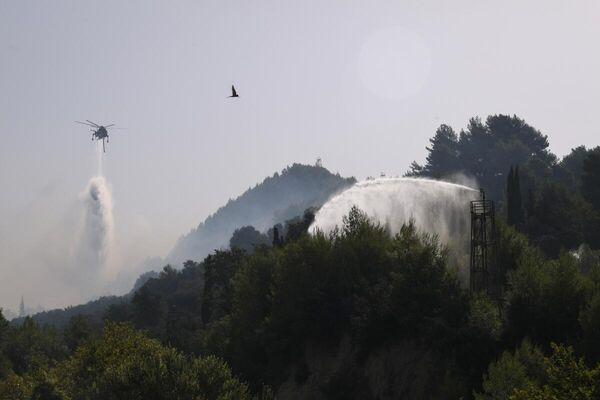 Εναέρια μέσα κάνουν ρίψεις νερού πάνω από δάσος στην Αρχαία Ολυμπία που καίγεται - Sputnik Ελλάδα