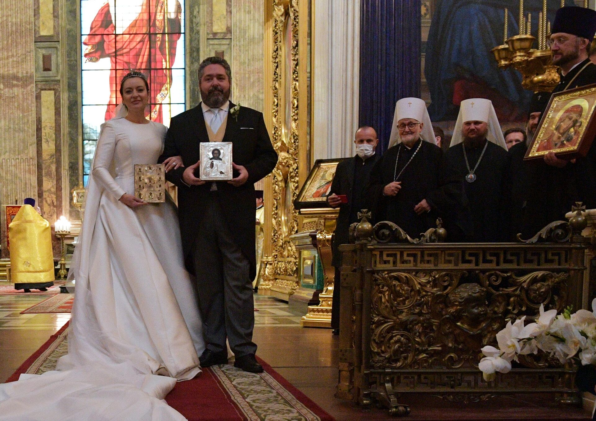 O Δούκας Γεώργιος Μιχαήλοβιτς Ρομανόφ και η Βικτόρια Ρομανόβνα Μπεταρίνι κρατούν εικόνες κατά τη διάρκεια της γαμήλιας τελετής  - Sputnik Ελλάδα, 1920, 01.10.2021