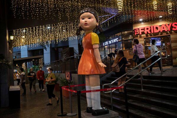 Μία κούκλα ύψους τριών μέτρων, εμπνευσμένη από τη σειρά του Netflix «Squid Game», έξω από εμπορικό κέντρο στην πόλη Κεζόν, στις Φιλιππίνες.  - Sputnik Ελλάδα