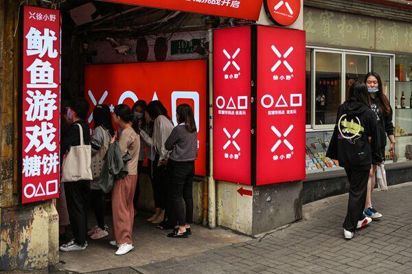 Πελάτες περιμένουν έξω από μικρό εμπορικό κατάστημα στη Σανγκάι, για τα «νταλγκόνα», το ζαχαρωτό μπισκότο που «πρωταγωνιστεί» σε ένα από τα παιχνίδια της σειράς Squid Game.  Η σειρά δεν είναι ακόμα διαθέσιμη στην Κίνα ωστόσο οι θαυμαστές της, προσπαθούν να αποφύγουν τους αυστηρούς ελέγχους του διαδικτύου και να «στρημάρουν» την παραγωγή καθώς και να αποκτήσουν υλικό, όπως τις χαρακτηριστικές φόρμες των παικτών.   - Sputnik Ελλάδα