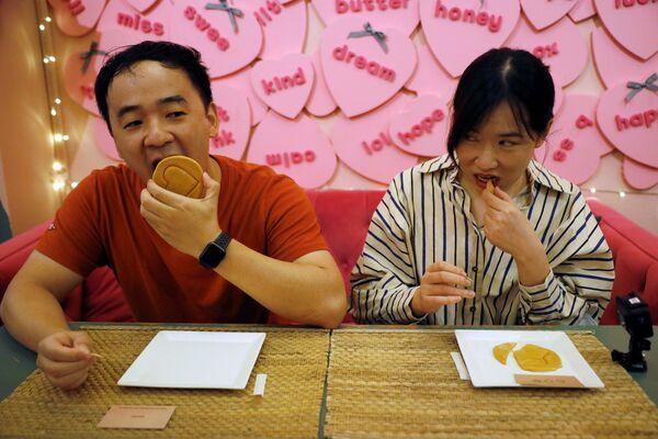 Ο 32χρονος Γουάνγκ Τσεν και η 27χρονη Ζανγκ Κι, δοκιμάζουν τις ικανότητές τους στην δοκιμασία με το μπισκότο, στο καφέ Brown Butter στην Σιγκαπούρη.  - Sputnik Ελλάδα