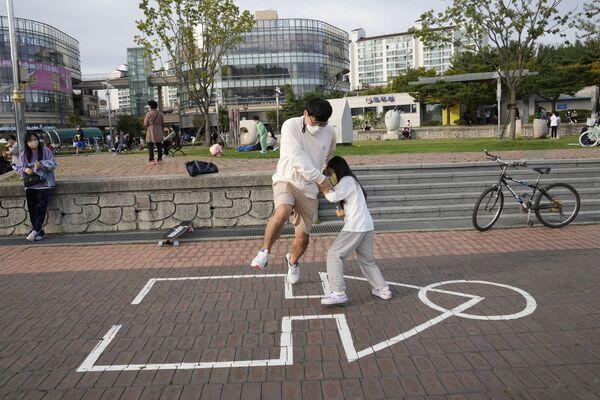 Ο Σον Κουάνγκ-γιε και η κόρη του, φορώντας προστατευτικές μάσκες, παίζουν το «Παιχνίδι του Καλαμαριού» σε πάρκο της Γκογιάν, στην Νότια Κορέα.  - Sputnik Ελλάδα