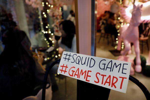 Μία πινακίδα αναφέρεται στην έναρξη του παιχνιδιού Squid Game, στο καφέ Brown Butter στην Σιγκαπούρη. - Sputnik Ελλάδα