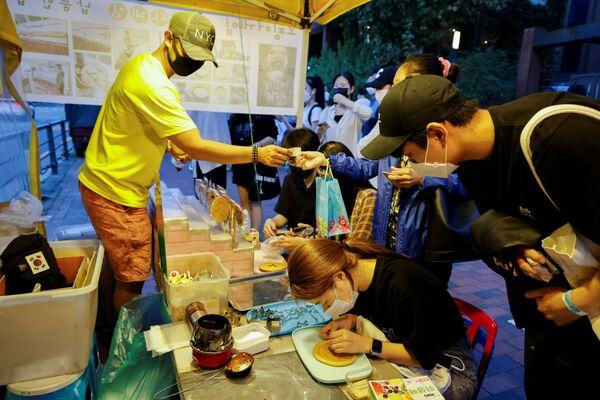Πωλητής στο δρόμο, δίνει στους πελάτες τα περίφημα γλυκίσματα «νταλγκόνα», στην Σεούλ της Νότιας Κορέας.  - Sputnik Ελλάδα