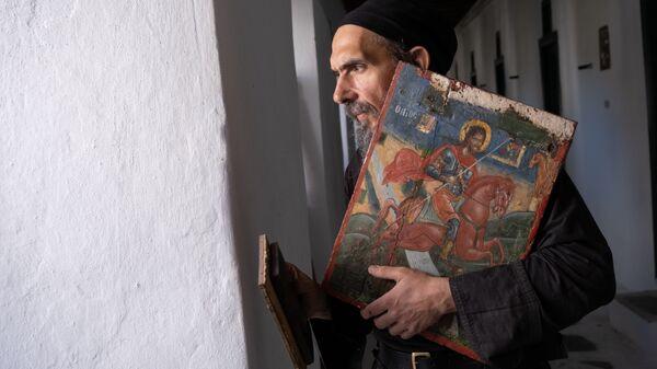 Отец Леонидас, настоятель православного монастыря Лонговардас на острове Парос архипелага Киклады в Греции, держит русскую икону с изображением святого великомученника Евстафия, датируемую 18 веком - Sputnik Ελλάδα