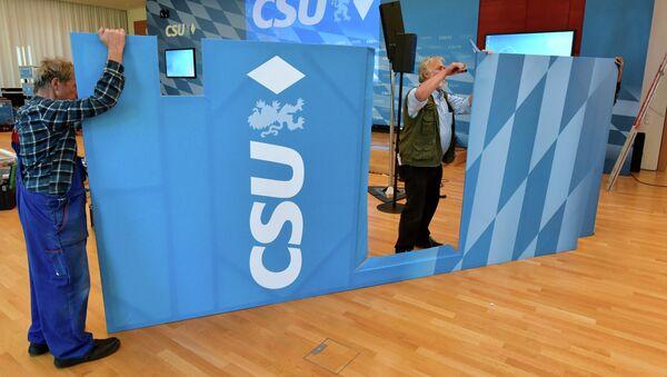 Εργαζόμενοι μεταφέρουν το λογότυπο του CDU - Sputnik Ελλάδα
