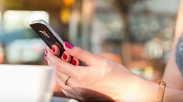 Γυναίκα κρατάει κινητό - Sputnik Ελλάδα