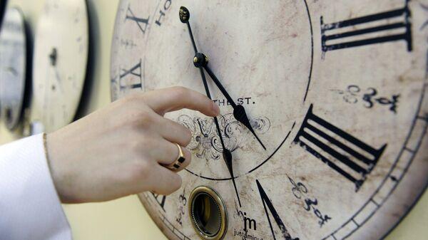 Υπάλληλος αλλάζει την ώρα σε θερινή σε κατάστημα στην Αγ. Πετρούπολη - Sputnik Ελλάδα