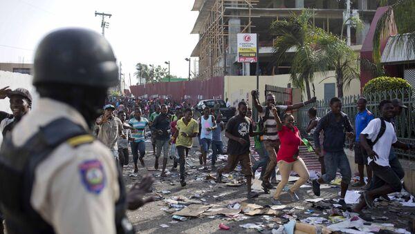 Αστυνομικός στην Αϊτή κοιτάζει το πλήθος να εισβάλει σε σούπερ μάρκετ στην Αϊτή - Sputnik Ελλάδα