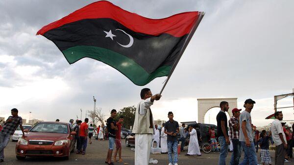 Λίβυος κρατάει την σημαία της Λιβύης - Sputnik Ελλάδα