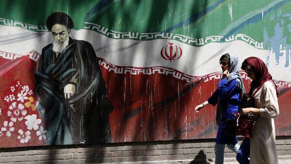 Ιρανές περνούν μπροστά από γκράφιτι που απεικονίζει τον Ανώτατο Ηγέτη της χώρας στην Τεχεράνη - Sputnik Ελλάδα