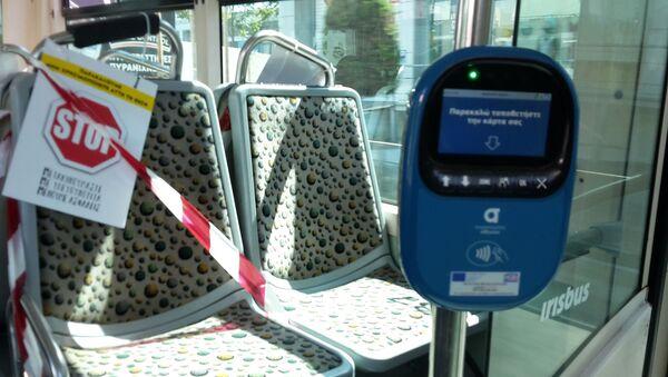 Πινακίδα για την τήρηση απόστασης ασφαλείας μεταξύ επιβατών και ακυρωτικό μηχάνημα εισιτηρίων σε λεωφορείο της ΕΘΕΛ - Sputnik Ελλάδα