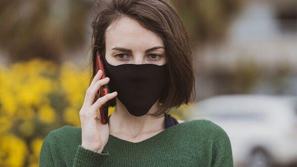Γυναίκα με μάσκα μιλάει στο κινητό - Sputnik Ελλάδα
